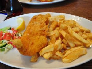 Fish and chips chutnají servírované na talíři...